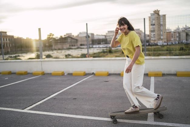 Foto grande angular de uma garota em um skate em um parque