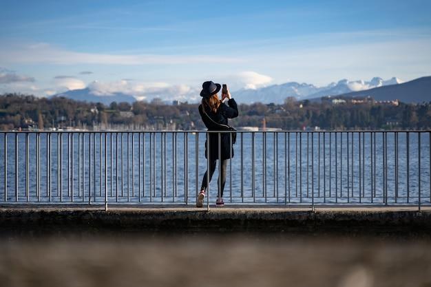 Foto grande angular de uma mulher em frente à água tirando fotos de montanhas