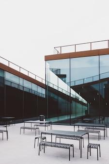 Foto grande angular de várias mesas colocadas em frente a um prédio de vidro