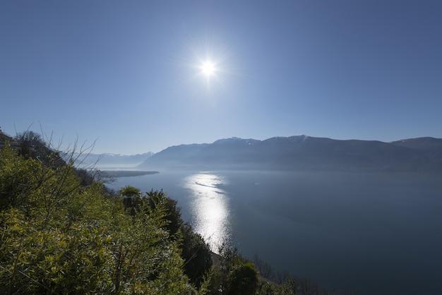 Foto grande angular do sol brilhando sobre a água e as montanhas