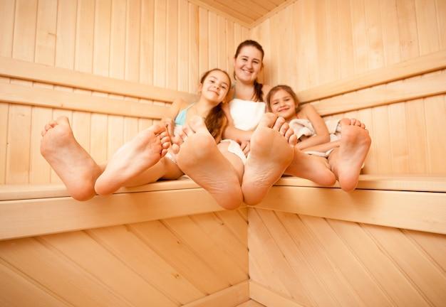 Foto grande angular dos pés da mãe e da filha na sauna