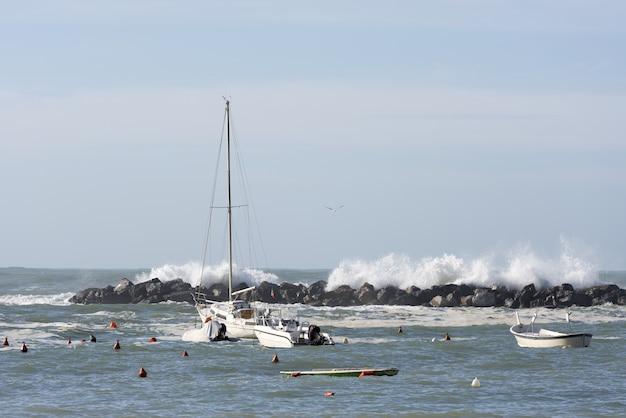 Foto hipnotizante das ondas atrás de barcos flutuantes durante o dia