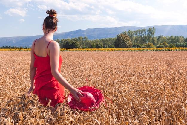 Foto hipnotizante de uma mulher atraente em um vestido vermelho em um campo de trigo