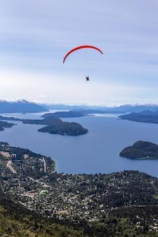 Foto hipnotizante do parapente voando sobre a bela paisagem