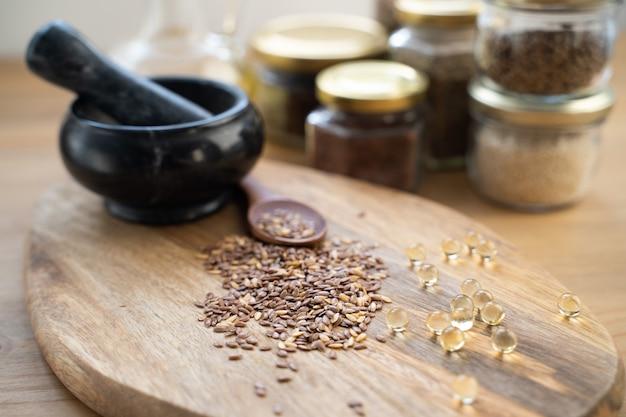 Foto horizontal com colher de pau cheia de sementes de linho ao lado de um pequeno frasco de vidro com óleo de linho e um monte de plantas de linho.