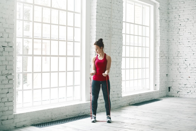 Foto horizontal da bela jovem europeia atlética com nó de cabelo malhando na academia, aquecendo os músculos com cinto de ioga, em pé no chão de madeira