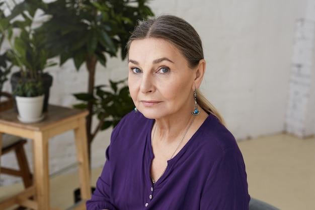 Foto horizontal da linda avó de olhos azuis de aparência europeia relaxando em casa, esperando os netos, vestindo uma camisa casual violeta e brincos, com expressão séria