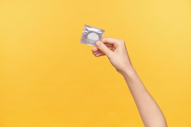 Foto horizontal da mão de uma jovem mulher de pele clara sendo levantada enquanto segura o pacote de prata com preservativo. mulher jovem prefere sexo seguro, posando sobre fundo laranja