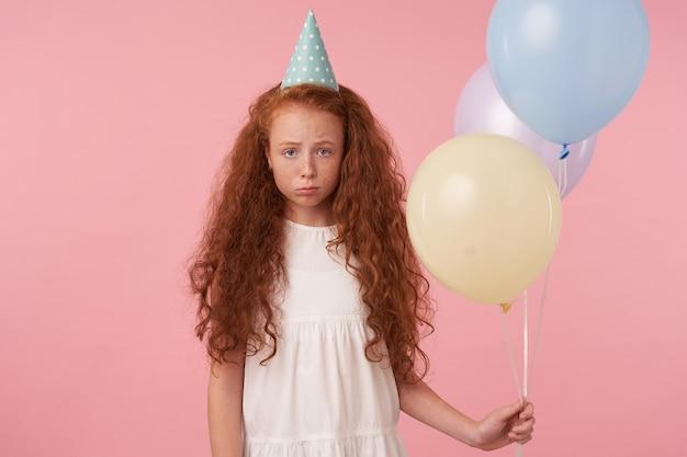 Foto horizontal da menina ruiva chateada com cabelo longo cacheado usando roupas festivas e boné de aniversário, olhando para a câmera com tristeza e franzindo os lábios, isolada sobre um fundo rosa com balões de ar