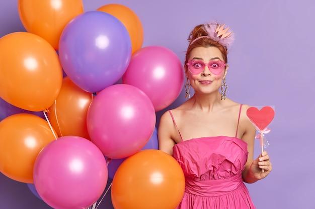 Foto horizontal da modelo feminina ruiva bonita olhando com alegria para a câmera e aceita os parabéns com uma expressão feliz segurando um doce em forma de coração
