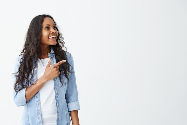 Foto horizontal da mulher afro-americana bonita e alegre, vestindo roupas casuais, mantendo o dedo indicador apontado para uma parede branca em branco, com espaço de cópia para o seu texto ou conteúdo publicitário