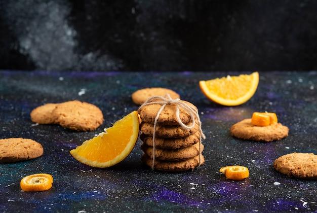 Foto horizontal da pilha de biscoitos caseiros com uma fatia de laranja sobre a superfície do espaço.