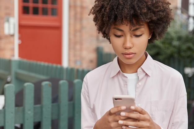 Foto horizontal de adolescente negra séria com penteado encaracolado, dando um passeio ao ar livre, segurando o telefone celular