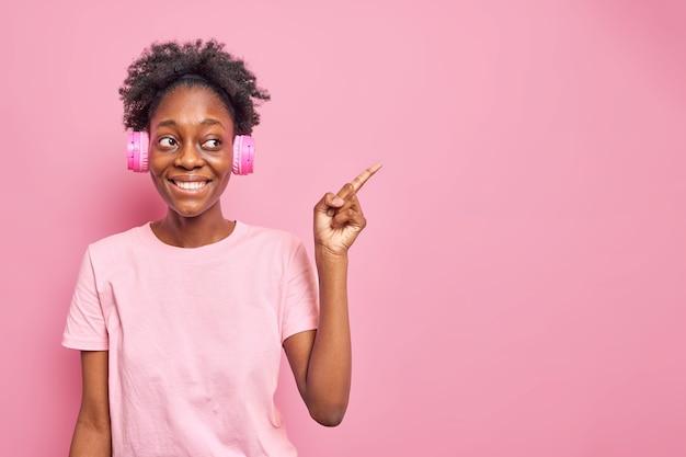 Foto horizontal de adolescente otimista com pele escura, expressão facial positiva indica espaço no espaço da cópia