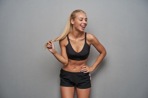 Foto horizontal de alegre jovem atraente loira em boa forma física, puxando seus longos cabelos e rindo alegremente enquanto posava sobre um fundo cinza claro
