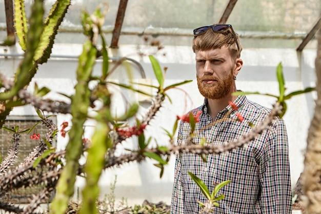 Foto horizontal de bonito jovem sério com barba espessa e camisa quadriculada