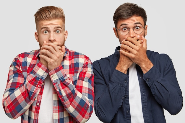 Foto horizontal de caras elegantes ou colegas de trabalho surpresos mantendo as mãos na boca, olhando para a câmera, sentindo espanto, ficando próximos um do outro