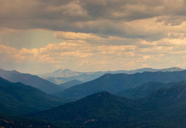 Foto horizontal de colinas em diferentes tons de azul e o céu nublado ao anoitecer