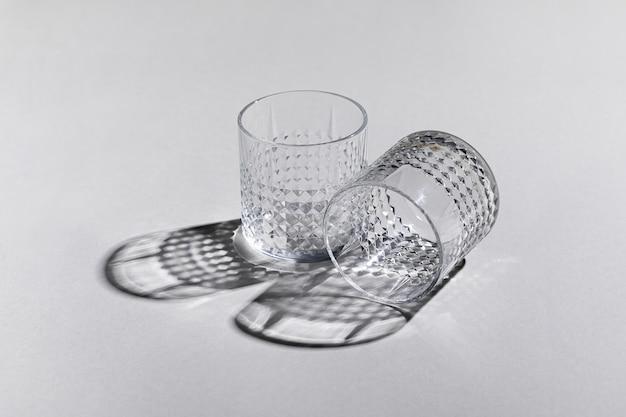 Foto horizontal de dois copos antigos vazios na superfície branca com sombras
