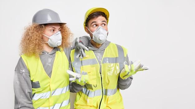 Foto horizontal de dois trabalhadores da construção civil usando máscaras protetoras de capacete e uniforme