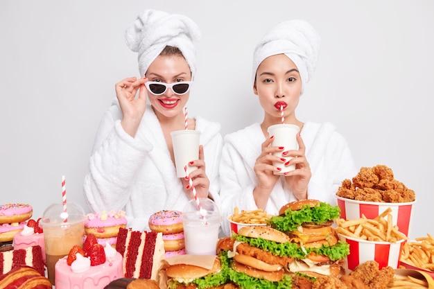 Foto horizontal de duas mulheres bebendo refrigerante com canudos e usando um roupão doméstico confortável