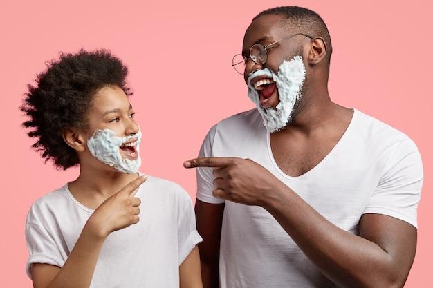 Foto horizontal de filho e pai felizes se divertindo juntos, indicando um ao outro, rindo com alegria