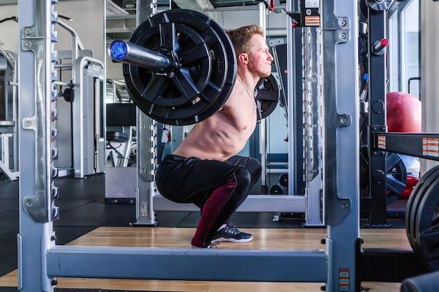 Foto horizontal de homem caucasiano realizando agachamentos com barra na academia coberta.