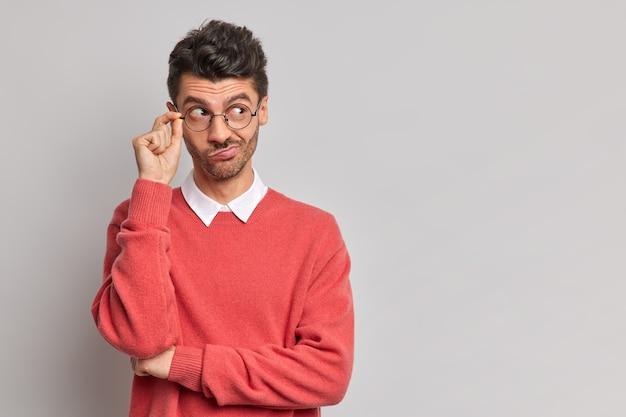 Foto horizontal de homem sério olhando pensativamente para o lado mantém a mão na borda dos óculos, bolsas, lábios concentrados à direita