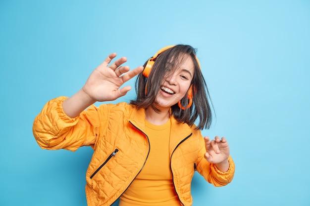 Foto horizontal de menina asiática positiva com cabelo castanho natural voando no ar, palmas das mãos, movimentos com ritmo de música desfruta de som de boa qualidade via fones de ouvido sem fio usa jaqueta