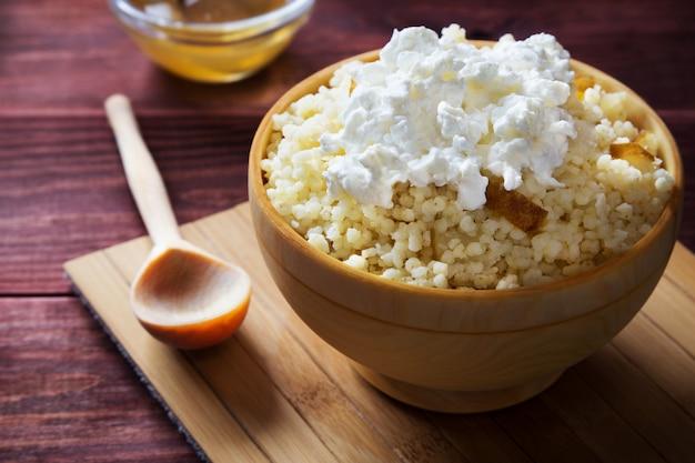 Foto horizontal de mingau de milho com pêra e queijo cottage