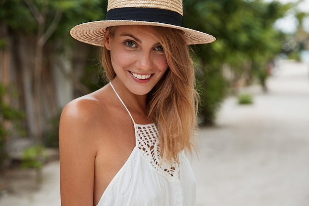 Foto horizontal de mulher bonita feliz com sorriso positivo, usa chapéu de verão e vestido branco, tem uma caminhada ao ar livre, desfruta de um bom descanso durante as férias e o sol quente. férias e estilo de vida