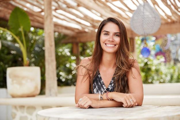 Foto horizontal de mulher bonita satisfeita com aparência agradável sentada no terraço do café, recriar em um país tropical com o namorado. turista relaxada posa em um restaurante ao ar livre durante o verão