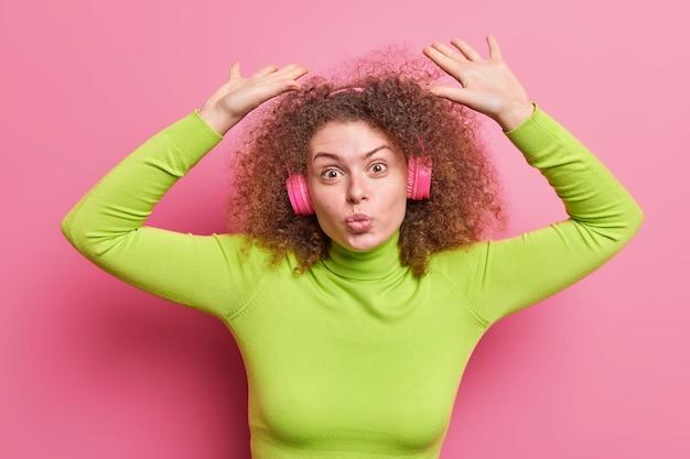 Foto horizontal de mulher de cabelo encaracolado mantém os lábios dobrados levanta os braços usa fones de ouvido sem fio com gola rolê verde isolada sobre parede rosa ouve nova faixa curtindo música legal da lista de reprodução