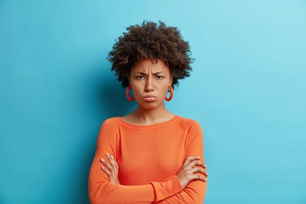 Foto horizontal de mulher de pele escura ofendida com cabelo afro com os braços cruzados e expressão ofensiva