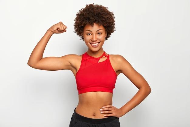 Foto horizontal de mulher de pele escura positiva mostra o bíceps, demonstra mão forte, tem corpo esguio, usa sutiã esportivo, sorri agradavelmente, isolado sobre fundo branco.