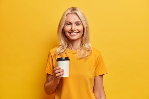 Foto horizontal de mulher europeia loira com sorriso agradável, maquiagem mínima segura xícara descartável de café vestida com camiseta casual