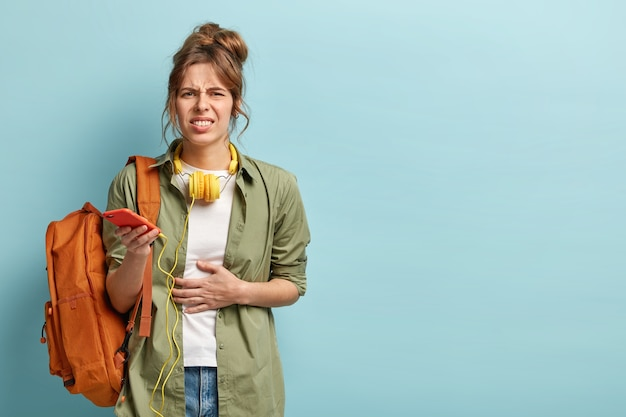 Foto horizontal de mulher insatisfeita com cólicas estomacais, diarreia, fome depois de caminhar, segurando o celular com fones de ouvido