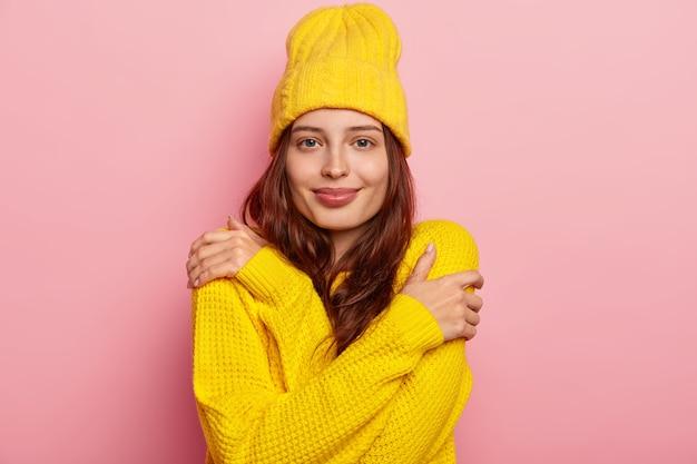 Foto horizontal de mulher jovem e atraente se abraça, tem cabelo comprido escuro, aparência terna, usa suéter e chapéu amarelo de inverno, posa contra o fundo rosa do estúdio.