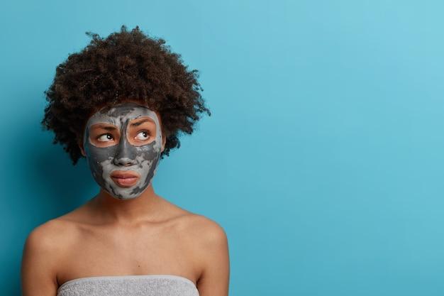 Foto horizontal de mulher pensativa com máscara nutritiva de argila aplicada, olha para o lado, tem os ombros nus, enrolada em uma toalha de banho, fica contra a parede azul com espaço de cópia. conceito de beleza.