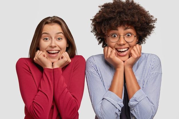Foto horizontal de mulheres alegres mestiças segurando o queixo