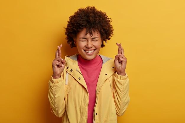 Foto horizontal de mulheres com esperança de boa sorte ou fortuna, antecipa resultados positivos ou milagres, fecha os olhos e cruza os dedos