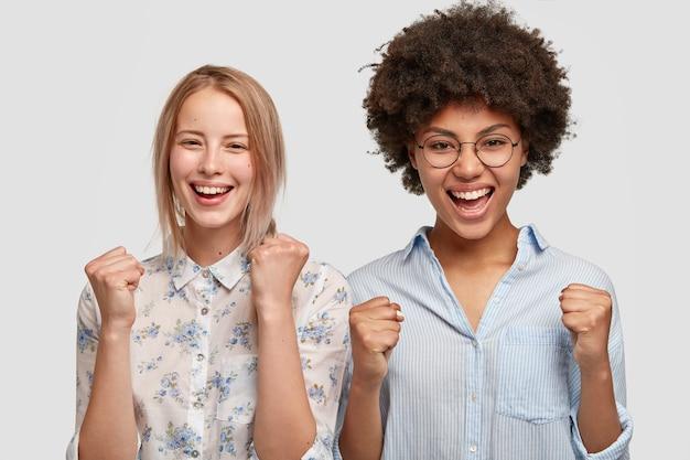 Foto horizontal de mulheres mestiças felizes cerram os punhos de felicidade, satisfeitas com o resultado do jogo, gritam por seu time favorito, têm expressões alegres, isolado na parede branca