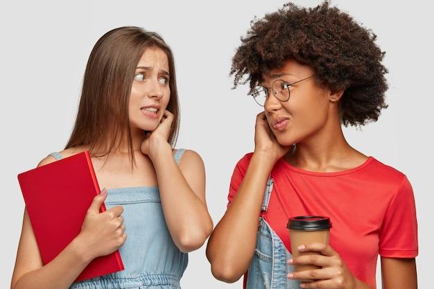 Foto horizontal de mulheres neuróticas olhando ansiosamente uma para a outra