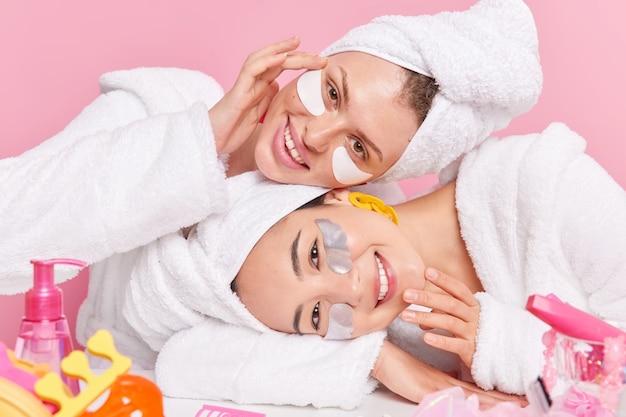 Foto horizontal de mulheres satisfeitas inclinando as cabeças, tocando uma pele saudável e macia, aplicando adesivos de beleza sob os olhos