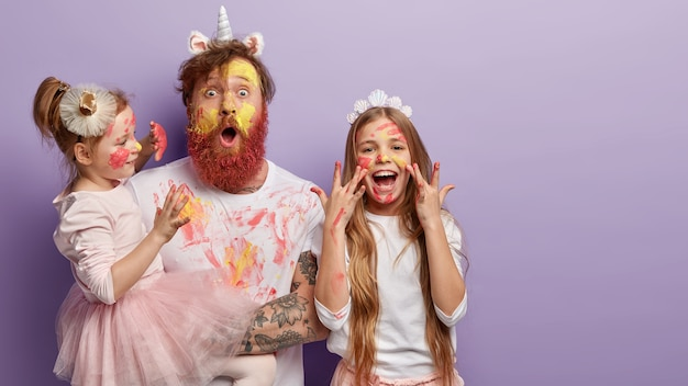 Foto horizontal de pai chocado com rosto amarelo pintado com aquarelas, duas crianças se divertem com o pai, expressões alegres, isoladas sobre parede roxa com espaço livre para promoção.
