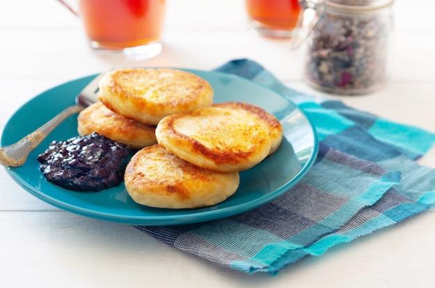 Foto horizontal de panquecas de queijo em um prato azul com chá e geleia