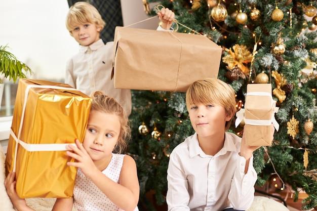 Foto horizontal de três irmãos fofos sentados na árvore decorada de ano novo segurando caixas com presentes de natal, sentindo-se impacientes, tendo olhares curiosos. infância feliz, alegria e festa