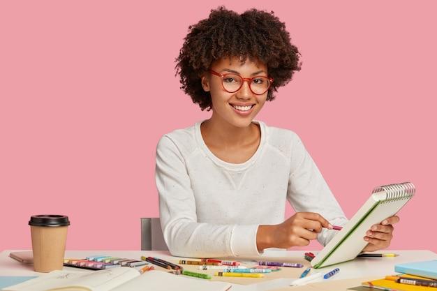 Foto horizontal de um alegre pintor afro-africano usando óculos de aro vermelho, fazendo esboços em caderno espiral com lápis, apreciando uma bebida aromática, rodeado de objetos fixos, sorri positivamente