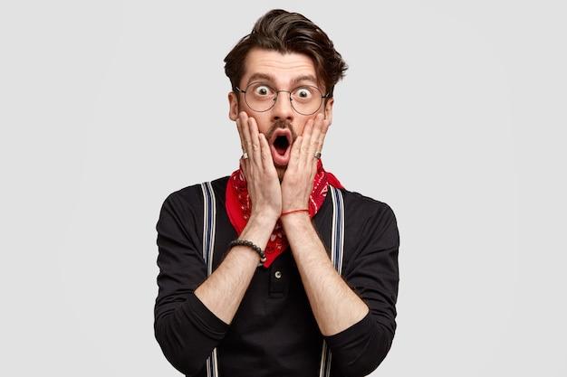 Foto horizontal de um atraente jovem barbudo cobrindo o rosto com as palmas das mãos e olhando com expressão chocada