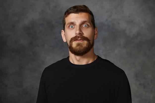 Foto horizontal de um belo homem adulto com olhos esbugalhados e barba por fazer posando de moletom preto arregalando os olhos, tendo uma expressão de pânico chocado, mostrando total descrença, terror ou medo